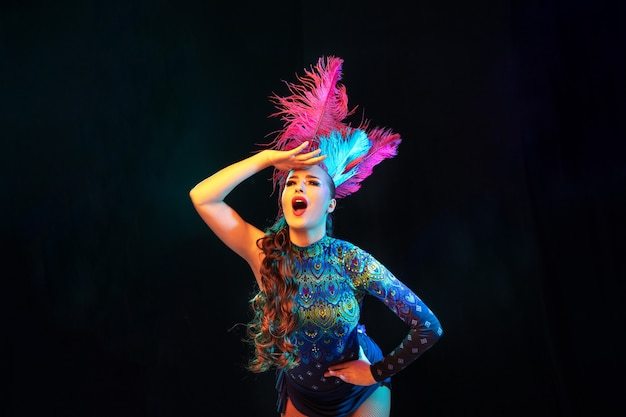 Beautiful young woman in carnival, stylish masquerade costume with feathers on black wall in neon