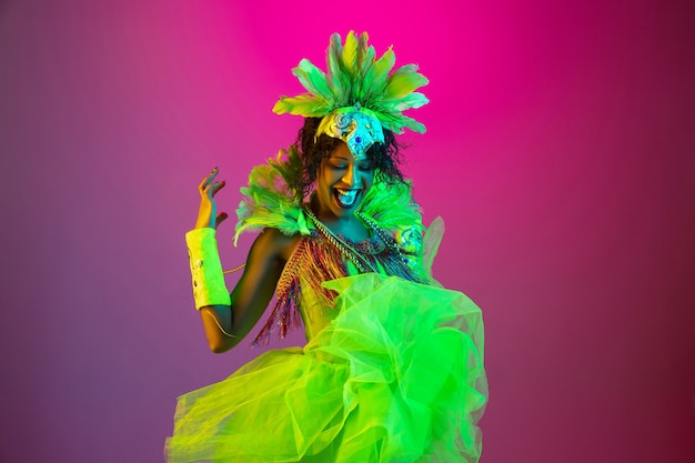 Beautiful young woman in carnival, stylish masquerade costume with feathers dancing on gradient background in neon light.