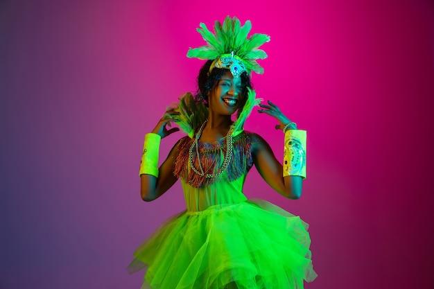 Bella giovane donna in carnevale, elegante costume in maschera con piume che ballano su sfondo sfumato in neon.