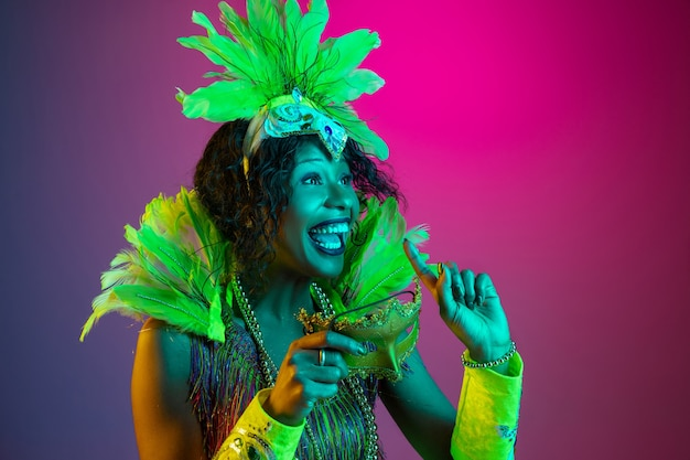 Beautiful young woman in carnival, stylish masquerade costume with feathers dancing on gradient background in neon.