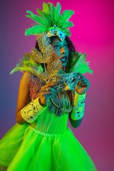 Bella giovane donna in carnevale, elegante costume in maschera con piume che ballano sulla parete sfumata in neon