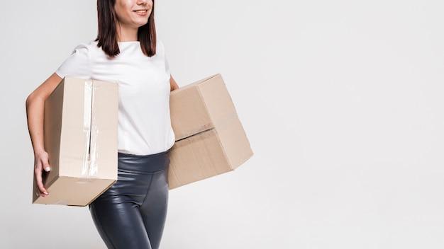 Beautiful young woman carrying cardboard boxes