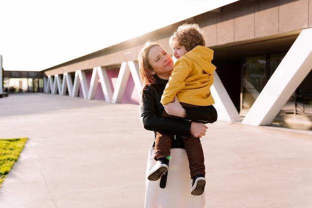석양에 그녀의 팔에 그녀의 3 살짜리 아들을 들고 아름 다운 젊은 여자. 출산 개념입니다. 아이들에게 사랑