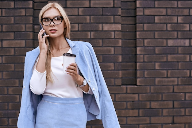 Beautiful young woman in casual clothes and eyeglasses is talking on her phone