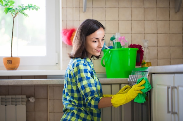 Beautiful young woman in casual wear is wiping electrical stove in the kitchen while cleaning her house.