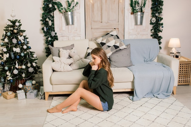 プレゼントを開けながら楽しんで、家でクリスマスを祝う美しい若い女性