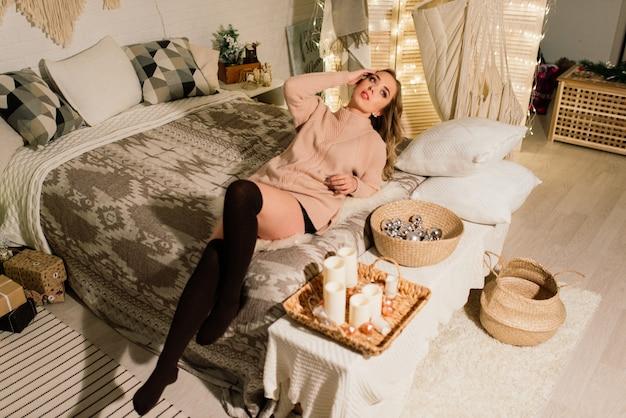 Красивая молодая женщина празднует рождество дома, развлекаясь при открытии подарков