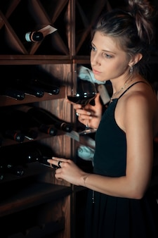 Beautiful young woman in the cellar with wines
