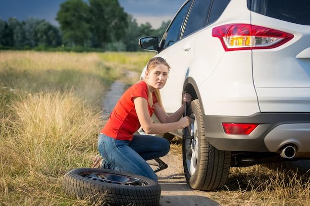 フィールドを通過する田舎道で車のホイールを変更する美しい若い女性
