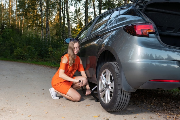 Beautiful young woman changing damaged wheel and fixing it