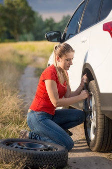 Beautiful young woman changing flat tire on the rural road