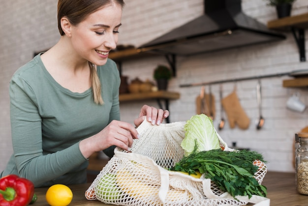 Beautiful young woman checking organic vegetables