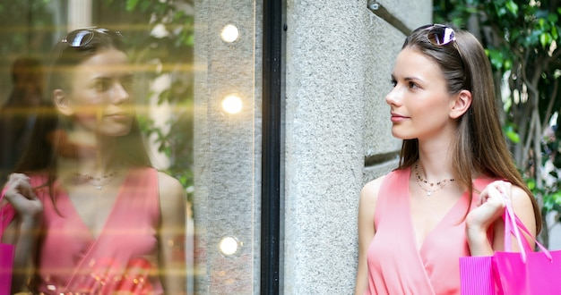 Beautiful young woman checking a store outdoor in a modern city setting
