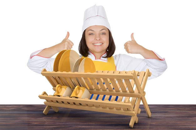 Beautiful young woman chef show thumbs up near bamboo kitchen dish drying rack with plates and mugs on a white background. 3d rendering
