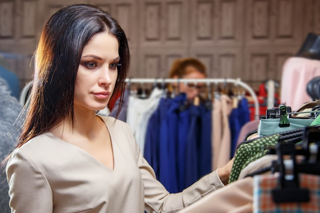 Beautiful young woman chooses dress in shop