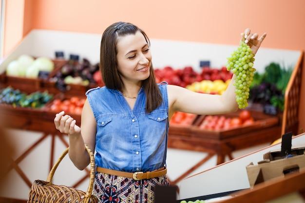 Красивая молодая женщина выбирает виноград в овощехранилище
