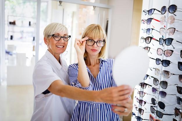 안경점에서 안경을 선택하는 아름다운 젊은 여성.