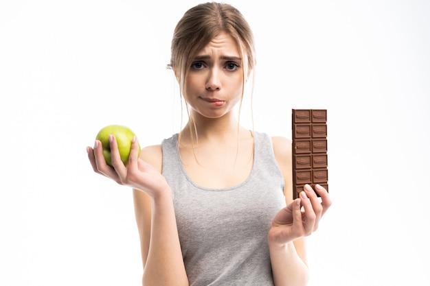 健康食品と不健康な食品のどちらかを選択する美しい若い女性