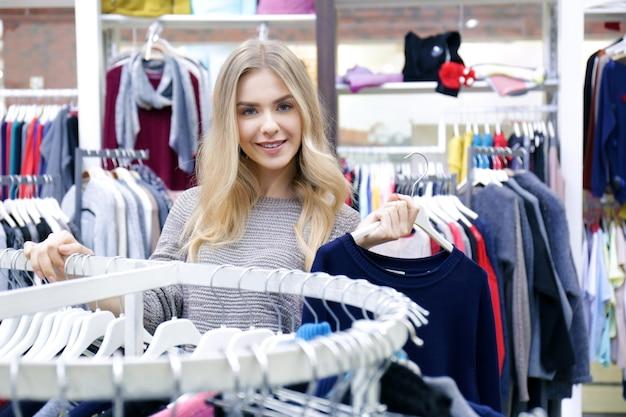 モダンな店で服を選ぶ美しい若い女性