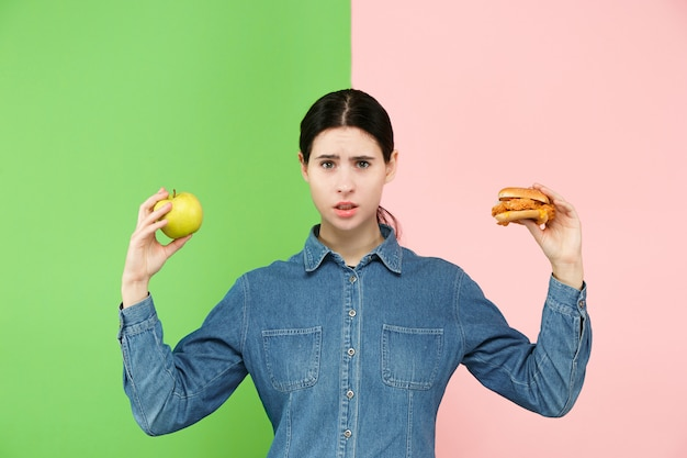 Beautiful young woman choosing between fruits and unhelathy fast food at studio.