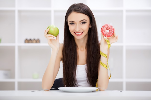 Beautiful young woman choosing between healthy food and junk food