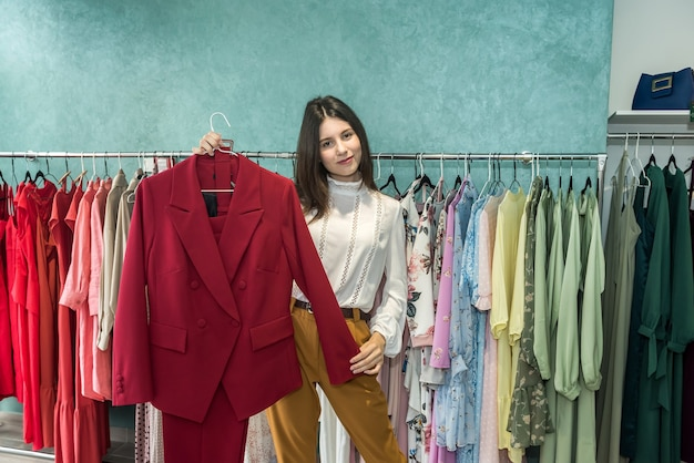 옷이 게에서 재킷을 선택 하는 아름 다운 젊은 여자. 새로운 스타일