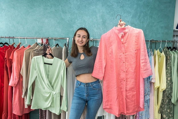 Beautiful young woman choosing jacket at clothes shop. new style