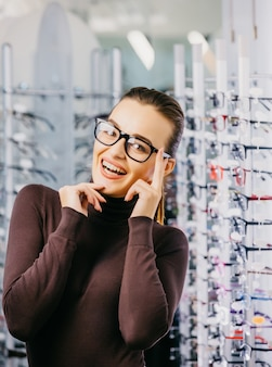 Beautiful young woman choosing new pair of spectacles in opticians store.