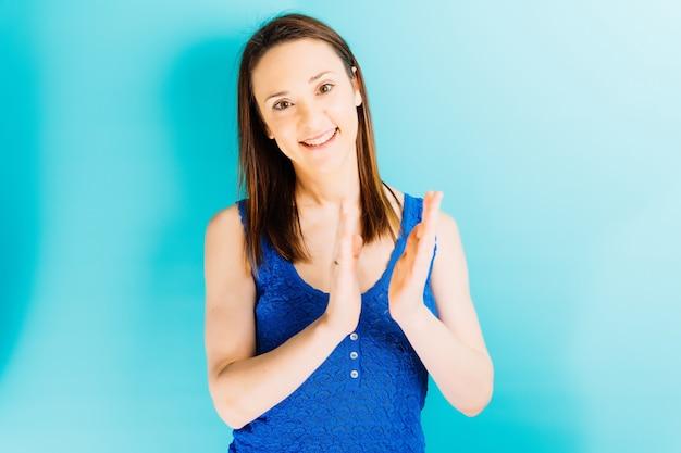 Красивая молодая женщина хлопает в ладоши с синим фоном и пространством для копирования