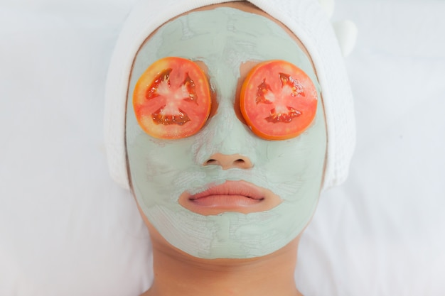 Beautiful young woman in clay mud mask on face covering eyes