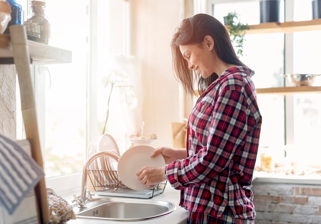 Beautiful young woman cleaning dishes