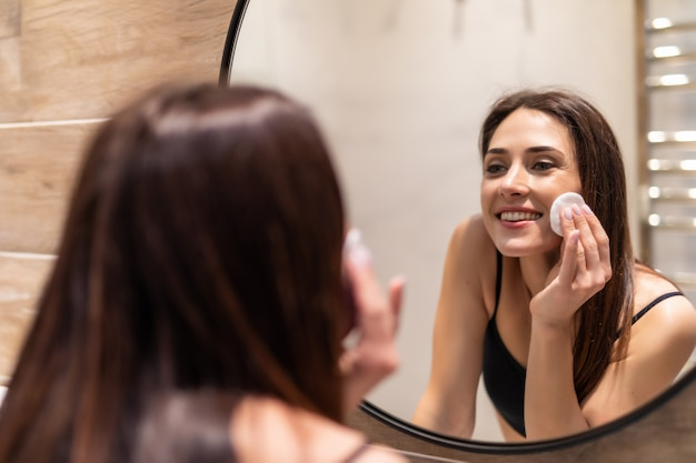 아름 다운 젊은 여자 목화 패드와 함께 그녀의 피부를 청소, 집 욕실에서 거울을보고.