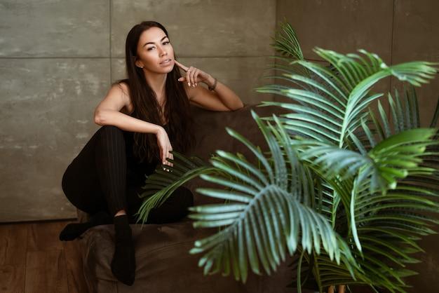 Портрет крупным планом красивой молодой женщины через зеленые листья цветка на серой стене