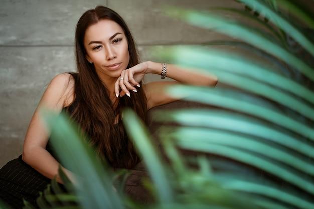 灰色の壁に花の緑の葉を通して美しい若い女性のクローズアップの肖像画