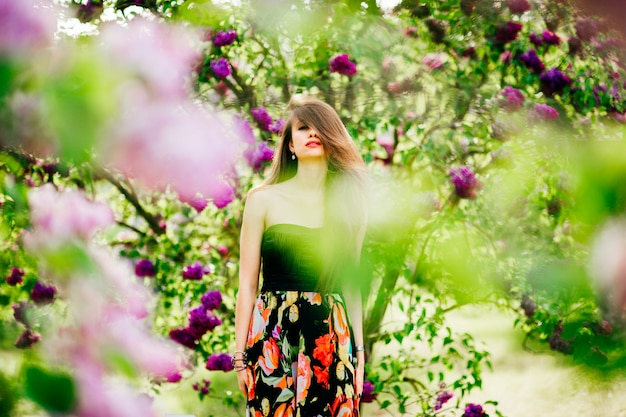 Beautiful young woman in colorful dress with long hair in summer  garden