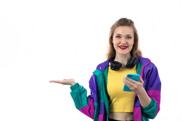 Beautiful young woman in colorful jacket and headphones and using smartphone