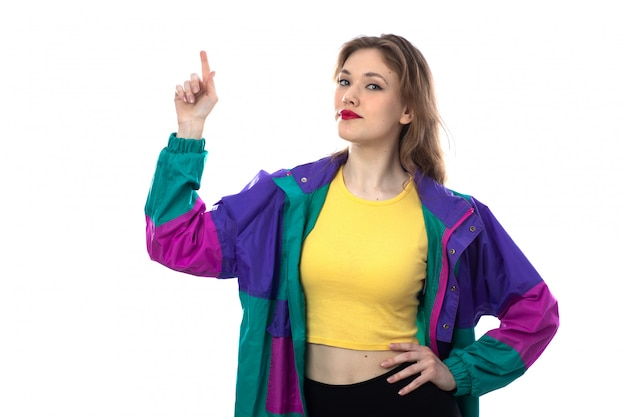 Beautiful young woman in colorful jacket pointing