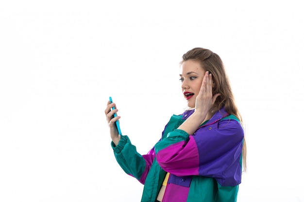 Beautiful young woman in colorful jacket using smartphone