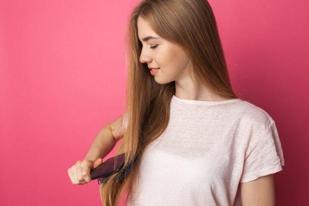 Красивая молодая женщина расчесывает блондинка длинные волосы красоты и прически, милая девушка улыбается