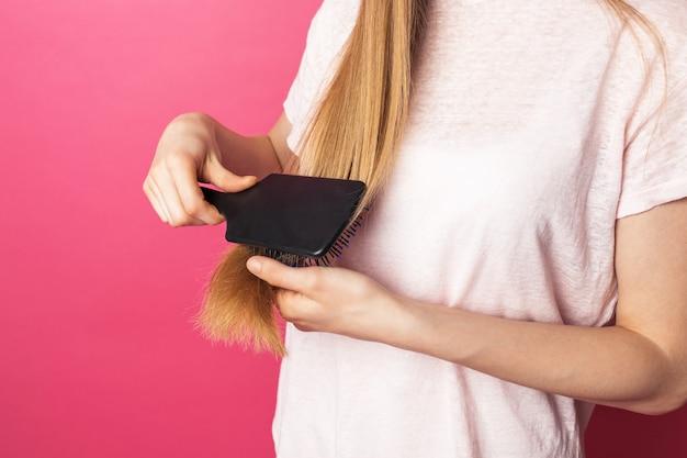 Красивая молодая женщина расчесывает блондинка длинные волосы красоты и прически