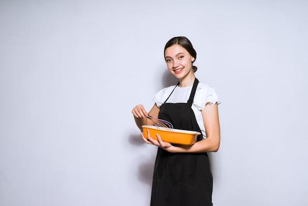美しい若い女性がおいしいパイを準備する黒いエプロンで調理します