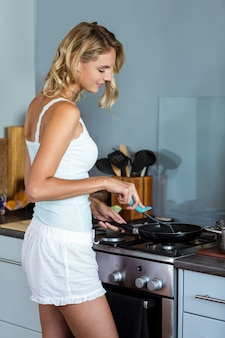 Beautiful young woman cooking food in kitchen