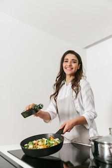 Красивая молодая женщина готовит здоровый ужин на кухне, используя сковороду