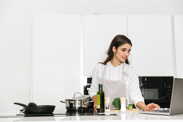 ラップトップコンピューターを見て、キッチンで鍋で健康的な夕食を調理する美しい若い女性