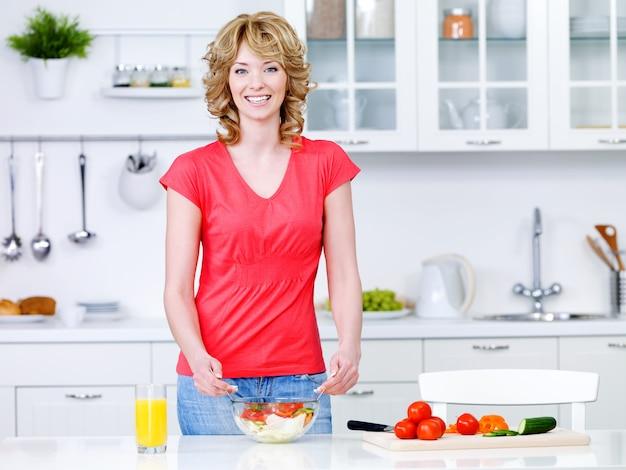 Bella giovane donna che cucina cibi sani in cucina - al chiuso