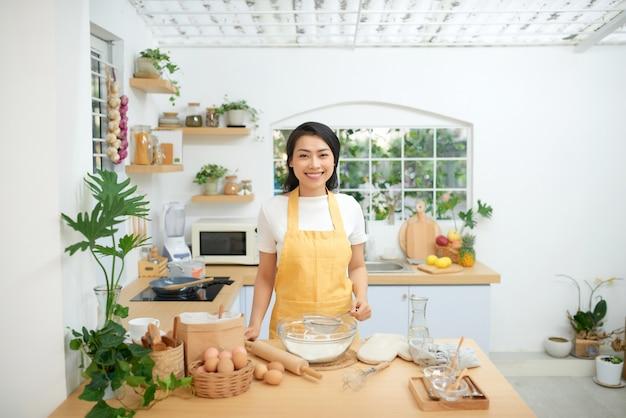부엌에서 패스트리를 요리하는 아름다운 젊은 여성