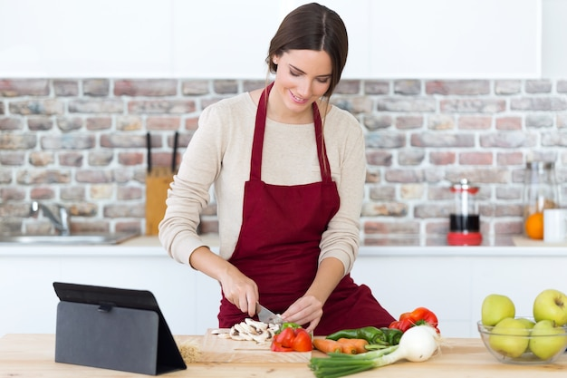 Beautiful young woman cooking and using digital tablet in the kitchen.