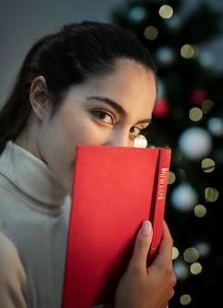 本で顔を覆っている美しい若い女性