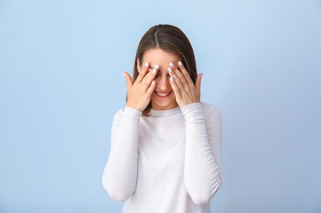 青の手で顔を覆う美しい若い女性