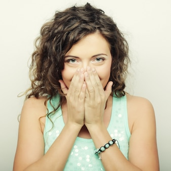 Beautiful young woman covering the face with her hand